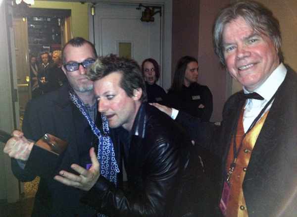 Tré Cool reaching for Donovan's Hall of Fame award backstage at the Public Hall in Cleveland. ©  Carlotta Hester, 2012.