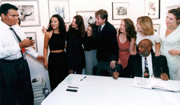 Howard Bingham getting ready to sign his book of photos of Ali at his Govinda Gallery exhibition while Ali charms the Govinda Girls with some magic. © Govinda Gallery Archive